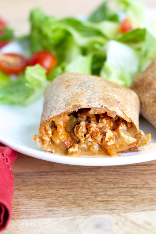 Veggie-packed baked burritos are stuffed with a hearty filling and baked to crispy perfection - and make an awesome freezer meal!